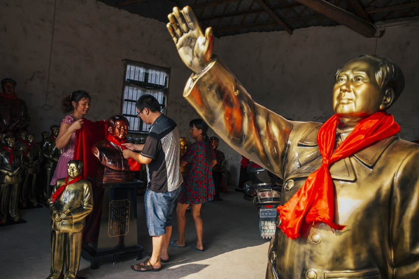 Xie Jinshan ties a red scarf around a newly minted Mao statue in Shaoshan, Sept. 16, 2015. Xu Xiaolin/Sixth Tone