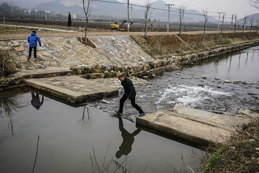 Ye steps across a stream while conducting a field investigation for his company in Zhuji, Dec. 23, 2015. Chen Ronghui/Sixth Tone