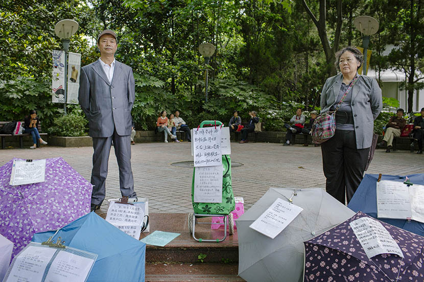 Parents stand behind umbrellas listing information on potential matches at the matchmaking corner in People's Park in Shanghai, May 17, 2015. Zhou Pinglang/Sixth Tone