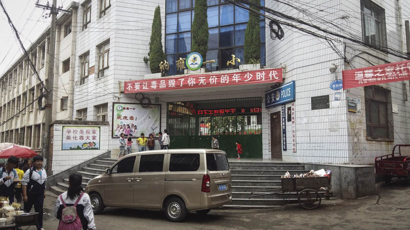 "A banner hanging above the entrance of Nayong No. 1 Primary School in Guizhou province says, ""Don't let drugs ruin your priceless childhood,"" May 6, 2015. Duan Yanchao/Sixth Tone"
