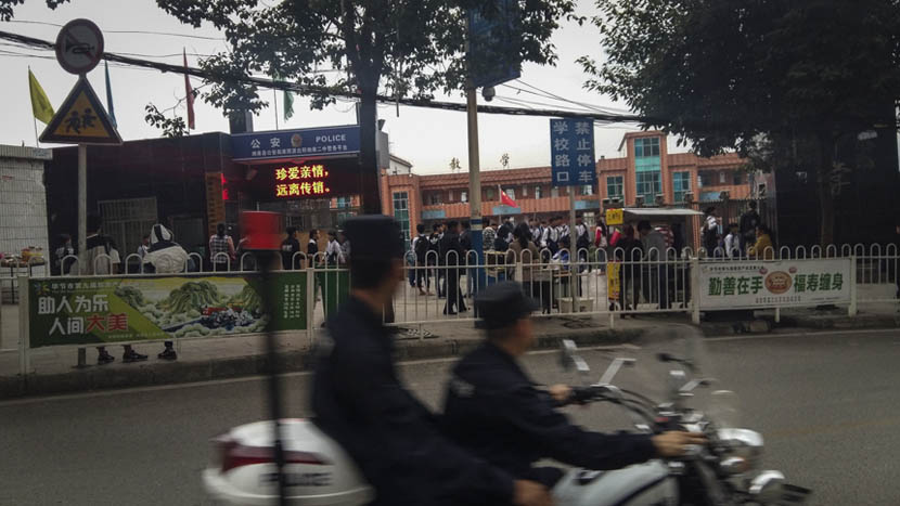 Two policemen patrol by motorcycle in front of Nayong No. 2 Middle School in Guizhou province, Nov. 24, 2015. Duan Yanchao/Sixth Tone