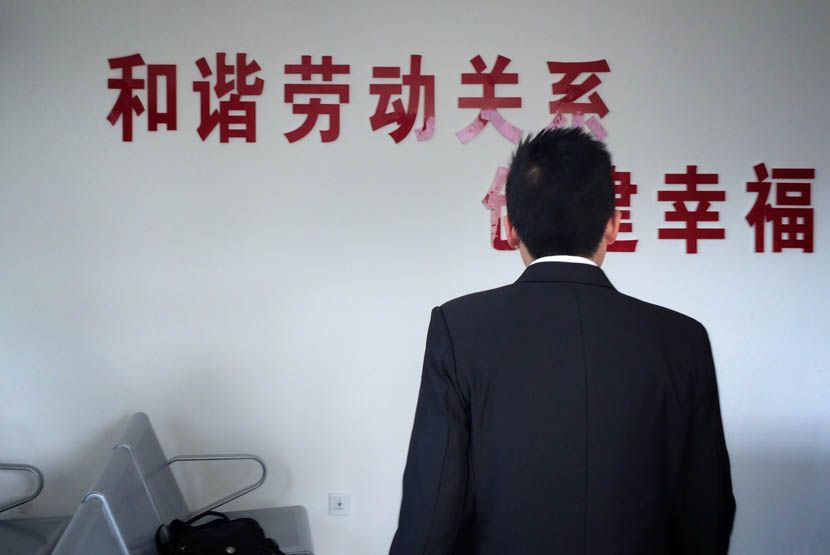 Mr. C stands in front of a slogan which reads 'harmonious work relationships' outside the courtroom in Guiyang, Guizhou province, April 8, 2016. Yang Xingbo, Li Jian/Guizhou City News for Sixth Tone