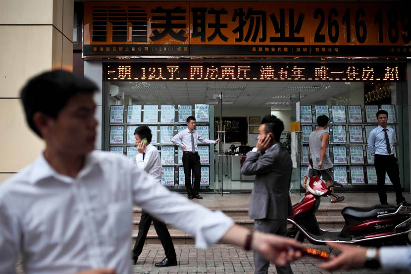 Agents stand in front of a real estate agency, in Shenzhen, Aug. 18, 2013. Zhou Pinglang/Sixth Tone