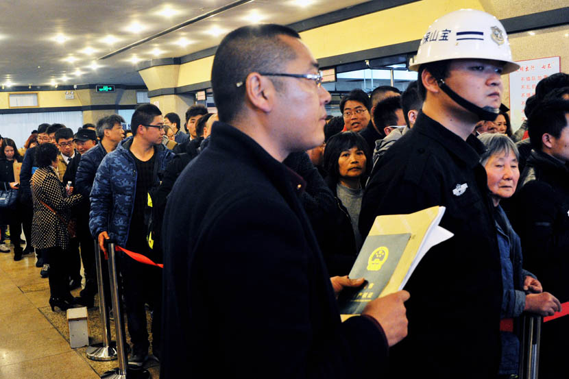 A man with a certificate of real estate ownership stands next to those who queue up for dealings at Baoshan Real Estate Trading Center, in Shanghai, Feb. 28, 2016. Yang Yi/VCG