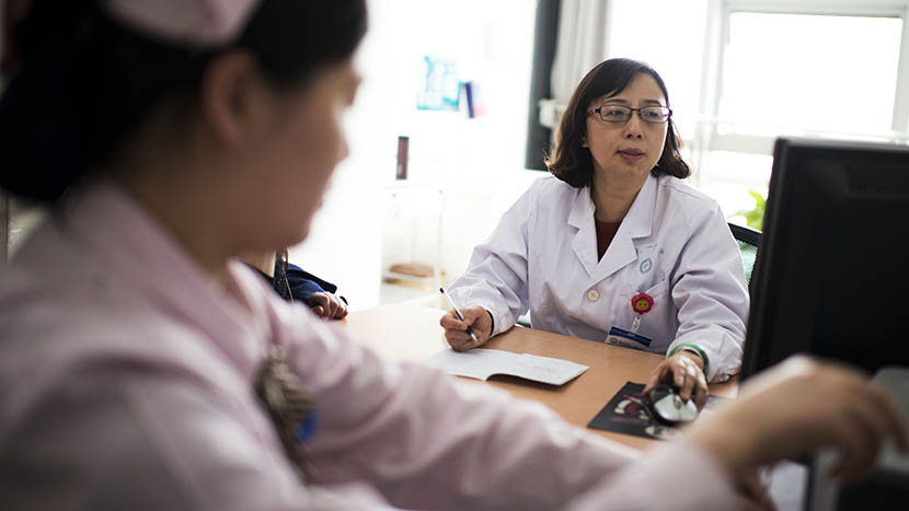 A senior doctor, Guo Yihong, in her office, in Zhengzhou, Henan province, March 24, 2016. Guo spends four to five minutes on average with each patient. She sees 80 to 90 patients per half day. Wu Yue/Sixth Tone
