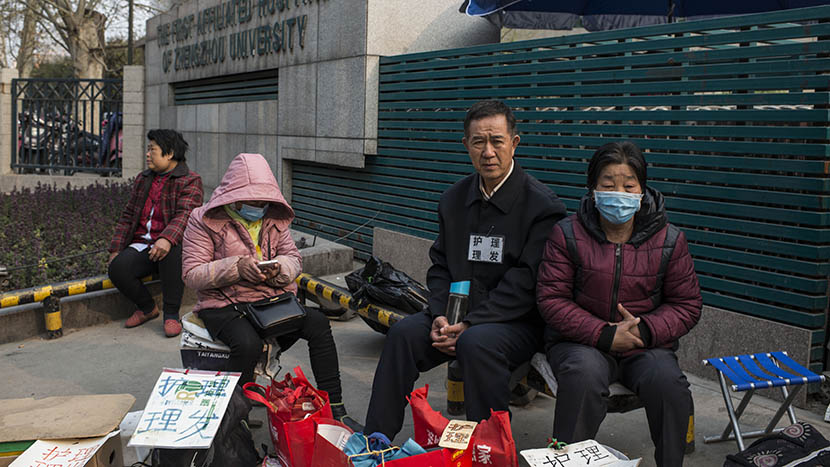A group of inpatient 'health carers' offer their services outside the hospital, in Zhengzhou, Henan province, March 25, 2016. Private caregivers make between 130 and 160 yuan per day. Wu Yue/Sixth Tone