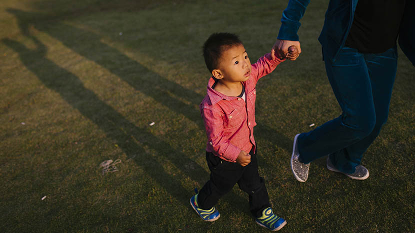 Tongtong is led by his nanny in a playground near his home, in Shanghai, Oct. 12, 2015. Zhou Pinglang/Sixth Tone
