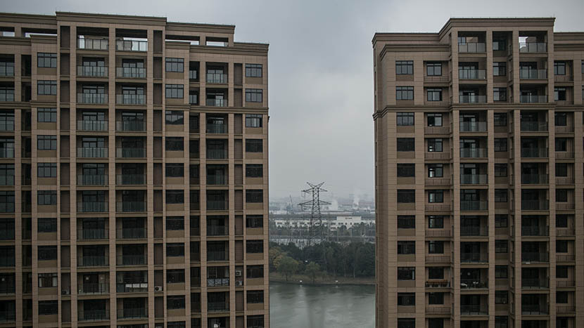 Factories seen through the window of a villager's new home in a high-rise residence, Shaoxing, Zhejiang province, Dec. 5, 2015. Chen Ronghui/Sixth Tone