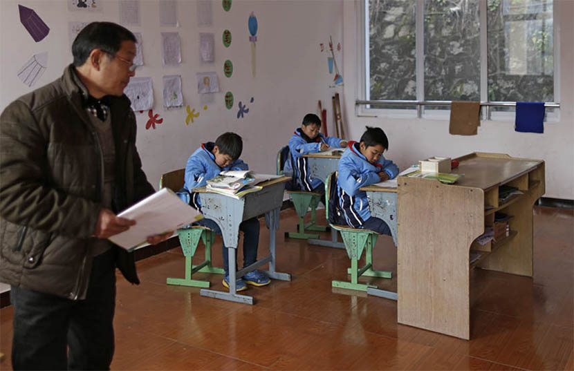 Three students study their textbooks in a classroom at Jingtian Primary School in Guangyuan, Sichuan province, Dec. 29, 2015. Cheng Yihui/Sixth Tone