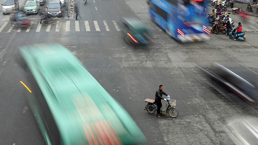 An e-bike speeds across a busy street in Zhengzhou, Henan province, 2014. Shalang/VCG