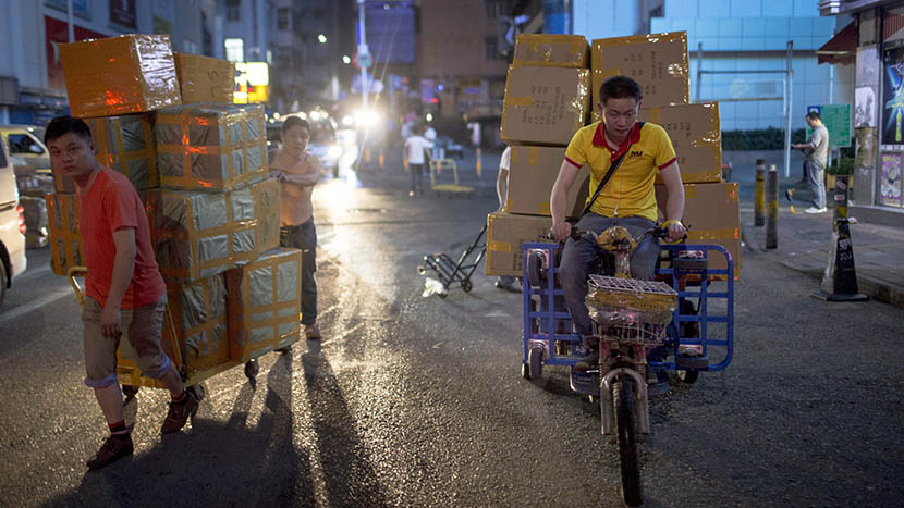 A courier carries packages on his electric freight tricycle at night, Shenzhen, Guangdong province, April 8, 2016. Zhou Pinglang/Sixth Tone