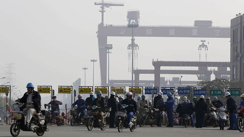 Workers from the Rongsheng Heavy Industries shipyard ride motorcycles and e-bikes home after their shifts, Nantong, Jiangsu province, Dec. 4, 2013. Aly Song/Reuters