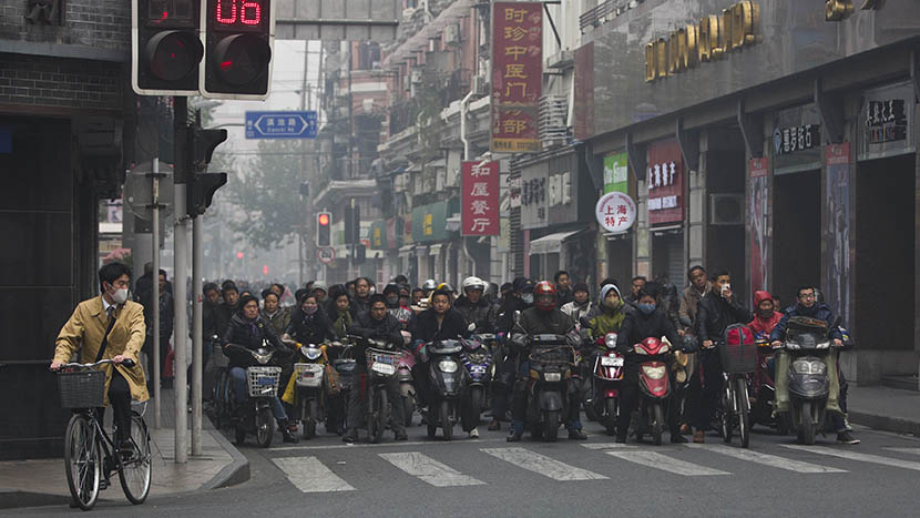 Local residents on e-bikes, motorcycles, and bicycles wait at an intersection on a hazy day in downtown Shanghai, Dec. 6, 2013. Aly Song/Reuters