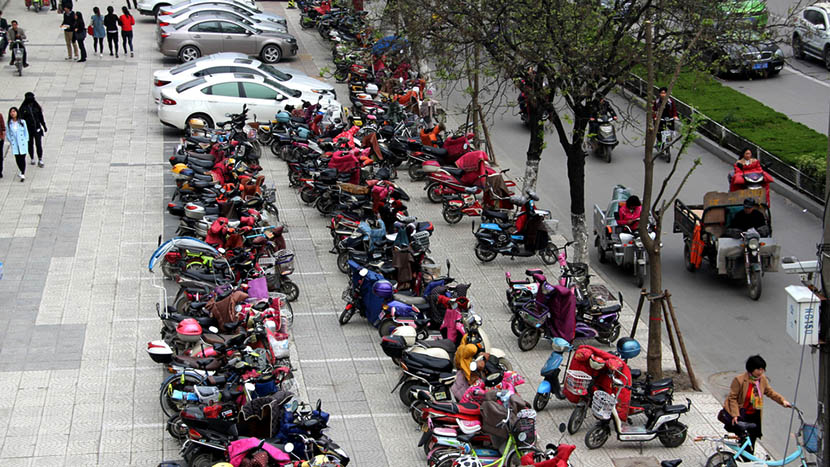 E-bikes, motorcycles, and cars parked on side of the road in Suzhou, Anhui province, April 11, 2016. IC