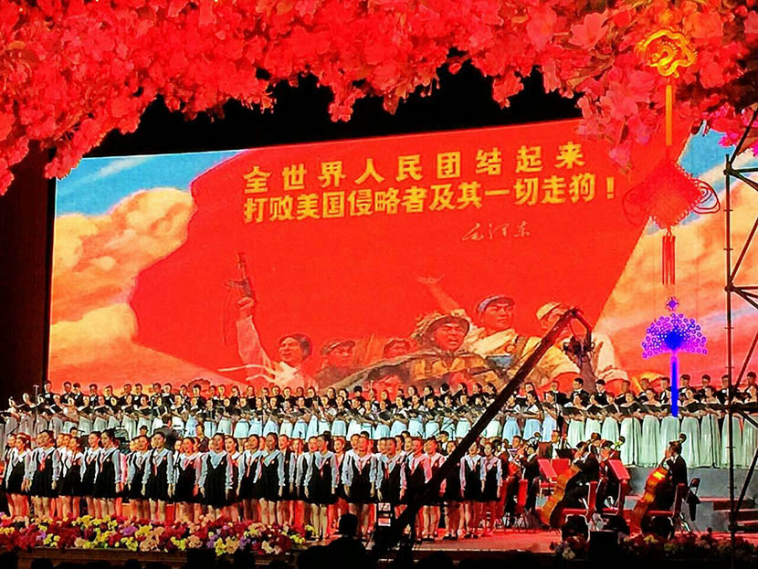 Performers in front of a backdrop featuring the slogan: 'The whole world must unite to defeat American invaders and their running dogs' at the 'In Fields of Hope' concert at the Great Hall of the People in Beijing, May 2, 2016. @PuBaoyi from Weibo