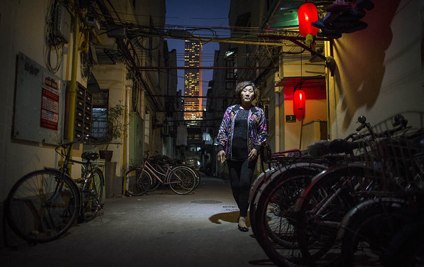 A woman in a lane on Changle Road is seen in front of an office building in Shanghai, May 11, 2016. Yang Shenlai/Sixth Tone