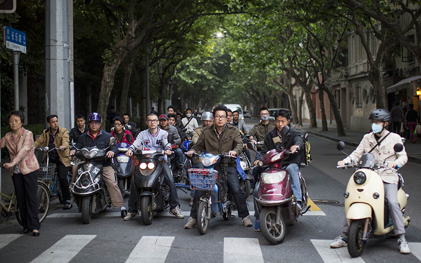 People on e-bikes, motorcycles, and bicycles wait at an intersection at the western end of Changle Road in Shanghai, May 11, 2016. Yang Shenlai/Sixth Tone