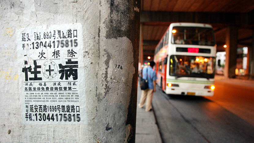 Illegal advertisement of sexually transmitted diseases pasted on a wall, Shanghai, Aug. 12, 2004. IC