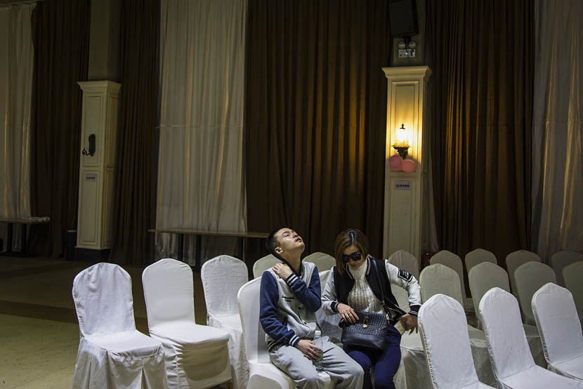 Sun Wenlin, seated with his mother, massages his neck after the wedding ceremony rehearsal in Changsha, Hunan province, May 16, 2016. Wu Yue/Sixth Tone