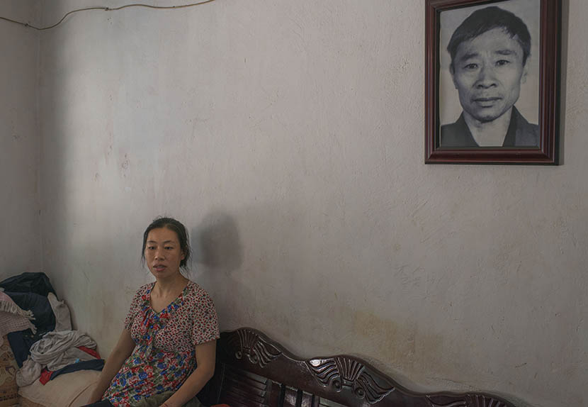 Gu Xia sits by a portrait of her deceased father in Jinghong, Yunnan province, April 17, 2016. Wu Yue/Sixth Tone