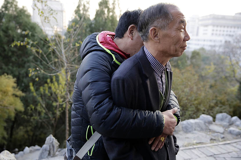 Peng Huijie is hugged by man at Dongdan Park in Beijing, Nov. 24, 2014. Dong Dalu/Sixth Tone