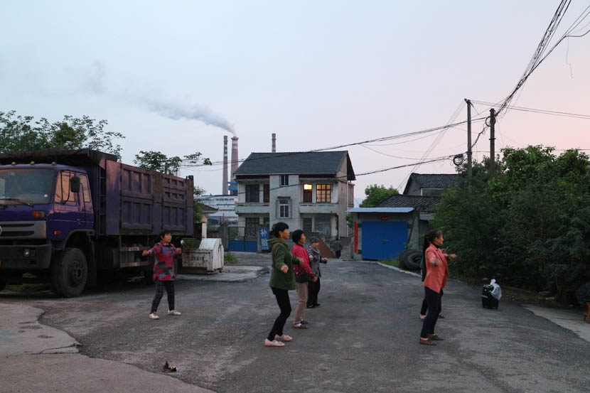 Women dance on a quiet street, with chimneys visible in the background, Yichang, Hubei province, April 17, 2016. Shi Yi/Sixth Tone