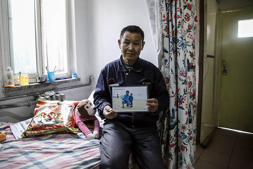 Fan Xifa, at his rented home near Beijing Children's Hospital, holds a photo of him and Zheng Zheng in Sanya, Hainan province, March 8, 2016. Huo Junjun/VCG