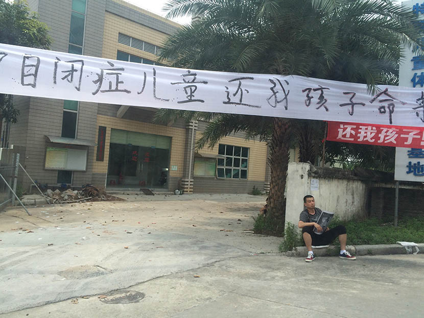 Jia Jia's father sits holding his son's photo under a banner that reads 'I want my son back' at the entrance to the autism rehabilitation center in Guangdong, Guangzhou province, May 2, 2016. Da Ba for Sixth Tone