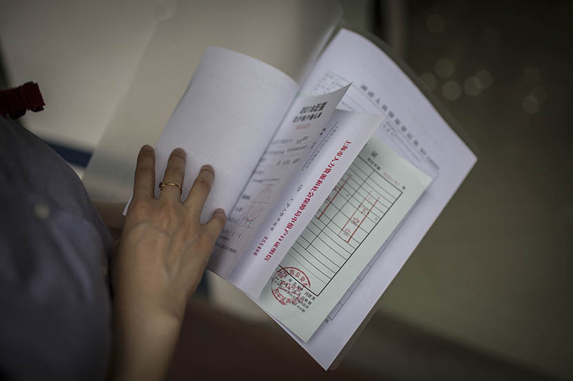 Lu Chen displays certificates and papers which are required in hukou application, Shanghai, May 5, 2016. Yang Shenlai/Sixth Tone