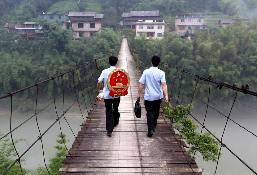 Two judges cross a bridge on their way to a village courthouse in Rongshui, Guangxi Zhuang Autonomous Region, May 21, 2015. Long Tao/VCG