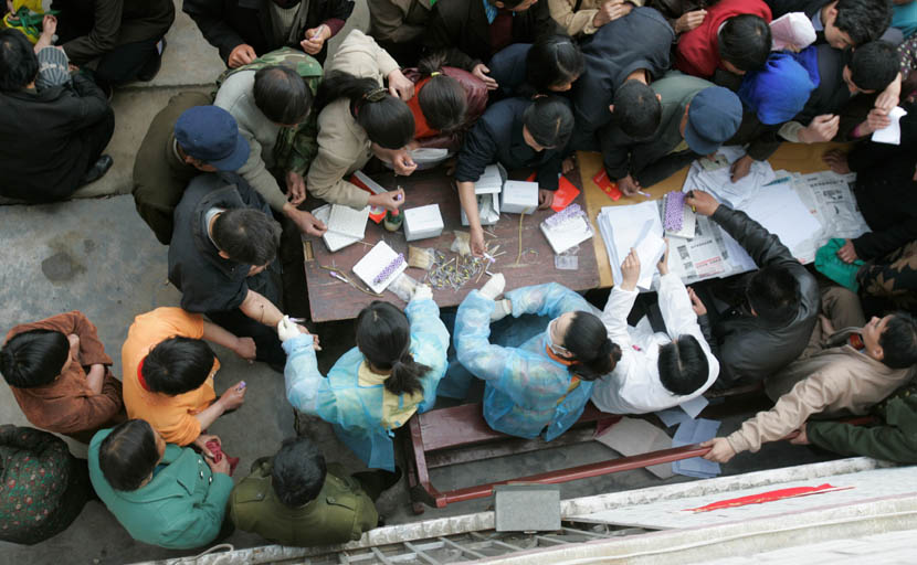 Villagers wanting to take HIV tests crowd around a table in Wenlou Village, Shangcai County, Henan province, April 2006. Xu Haifeng/Sixth Tone
