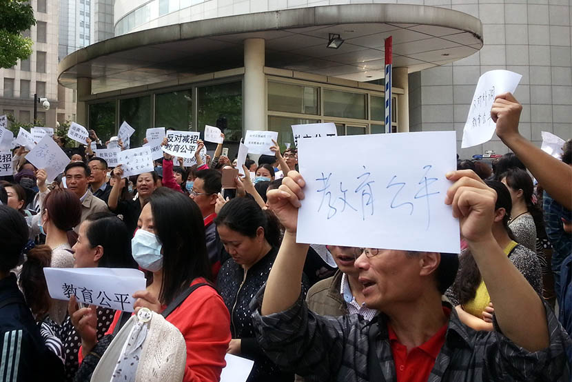 "Parents protest against the new policy as they hold slogans such as ""Equality for education,"" in Nanjing, Jiangsu province, May 14, 2016. Liu Birong/IC"