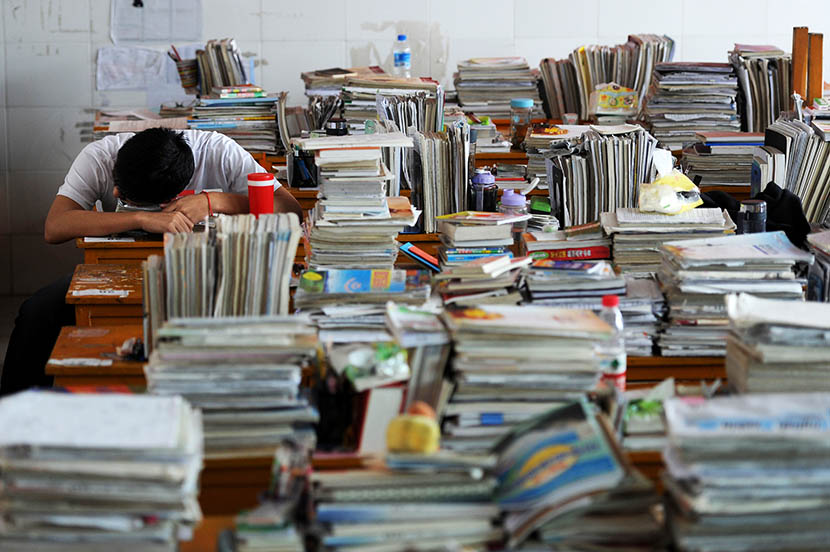 A senior high school student surrounded by piles of books sleeps on the desk in Maotanchang High School in Liuan, Anhui province, June 5, 2013. Wu Fang/VCG