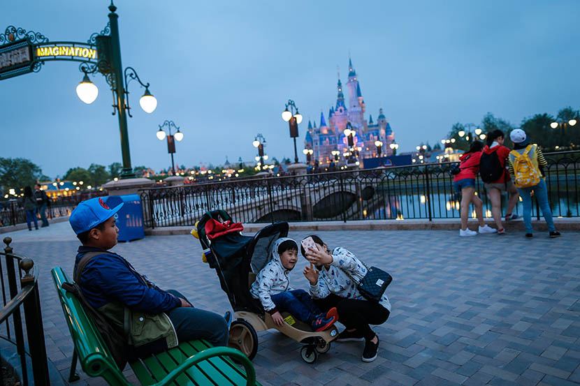 A woman takes a selfie with her son at Shanghai Disneyland during its soft opening, May 13, 2016. Liu Xingzhe/Sixth Tone