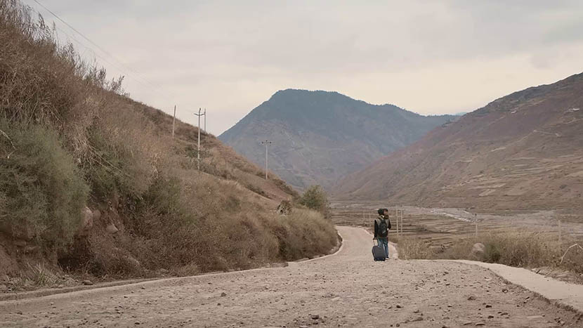 A still from 'The Verse of Us' shows poet worker Jike Ayou carrying a young child as he leaves his hometown for manual work. Courtesy of MeDoc.