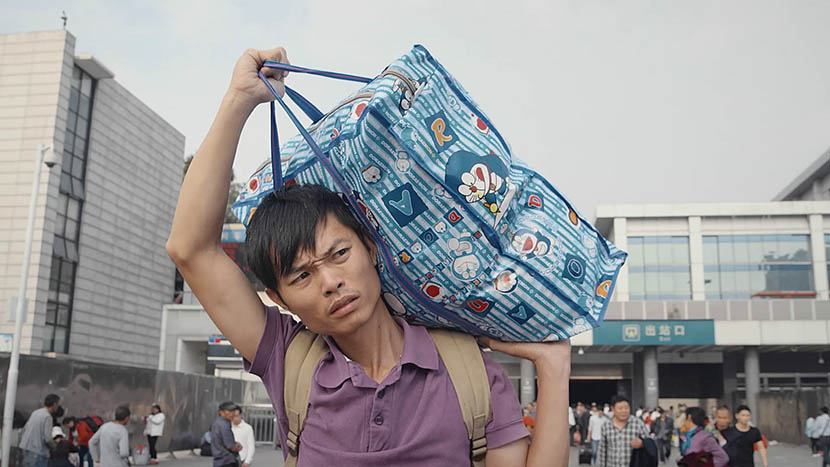 A still from 'The Verse of Us' shows poet worker Wu Niaoniao carrying luggage through Guangzhou as he looks for work. Courtesy of MeDoc.