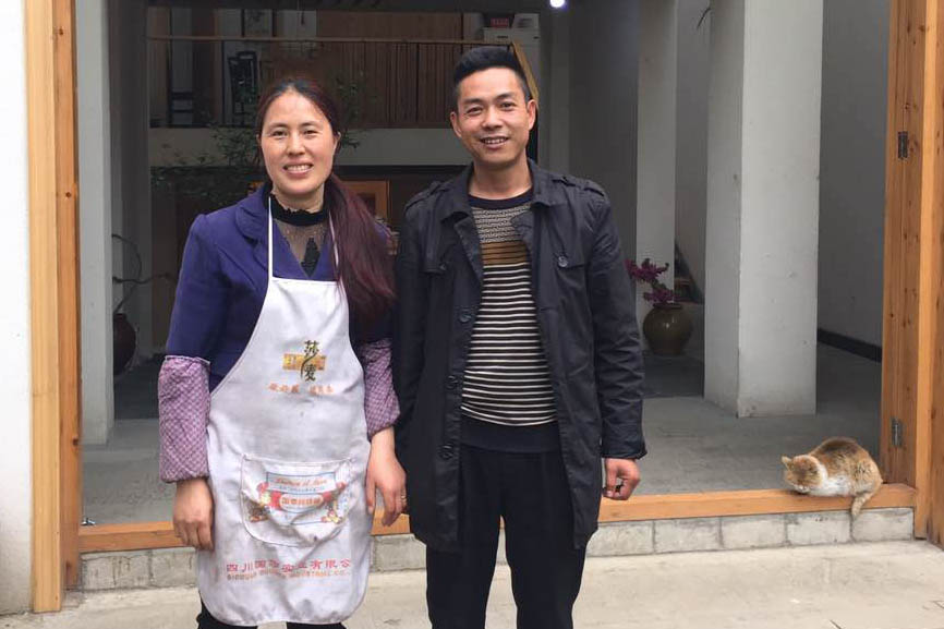 Tian Yuxia and her husband Li Dehua pose in front of the new house, 'Sister Tian's home' in Xueshan, Sichuan province, April 11, 2016. Wu Haiyun/Sixth Tone