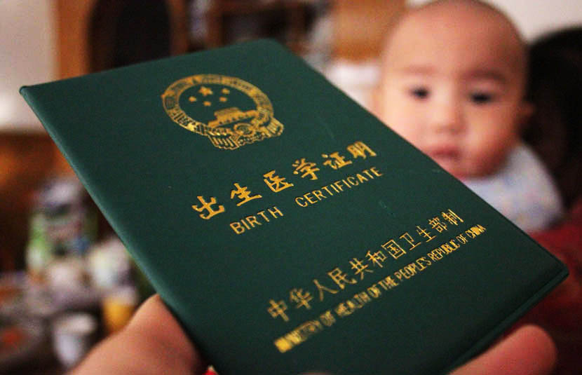 A birth certificate and its owner in Shiyan, Hubei province, Dec. 4, 2013. Zhang Xinjun/IC