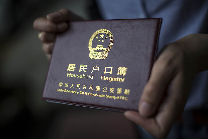 A woman holds her household registration document, or 'hukou,' in Shanghai, May 5, 2015. Yang Shenlai/Sixth Tone