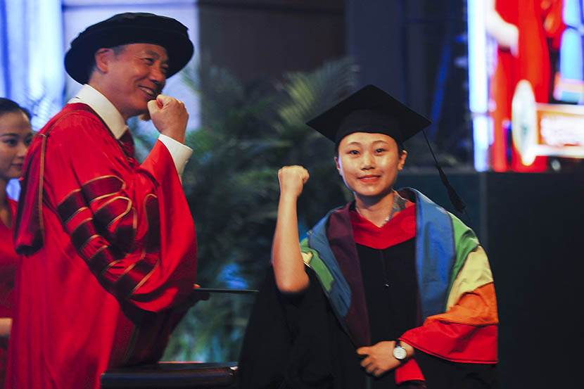 Wan Qing, wearing a rainbow flag, gestures during her graduation ceremony at Sun Yat-sen University in Guangzhou, Guangdong province, July 4, 2015. Chen Ying/VCG