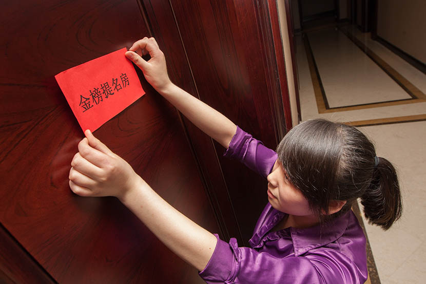 'This room brings good luck to pass the exam,' says the red envelope being stuck to the door of a guest's room by a hotel staff member, May 30, 2013. Yangguang/VCG