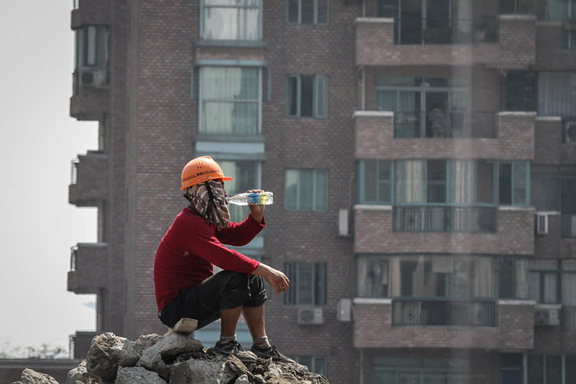A worker drinks from a water bottle on a construction site in Shanghai, Aug. 7, 2013. Yuan Ding/VCG
