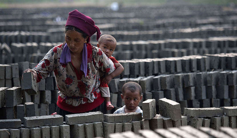 A woman of the Yi people from Liangshan works at a brickyard while carrying her son on her back, Huaian, Jiangsu province, June 22, 2012. IC