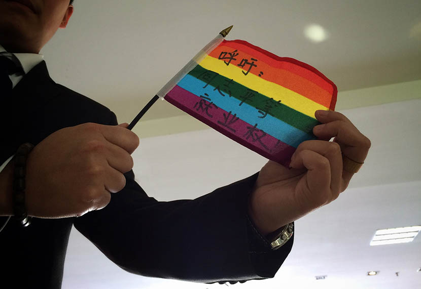 Mr. C displays a rainbow flag that reads 'Call for equal employment rights for LGBT' before the court hearing in Guiyang, Guizhou province, April 8, 2016. Wang Bei/VCG