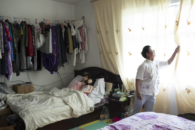 Yu Zhenguo opens a window while his two dolls lie in bed at his villa in Huishui, Guizhou province, May 19, 2016. Xu Haifeng/Sixth Tone