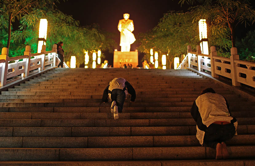 Two senior high school students kneel toward a Mao Zedong statue three days before the college entrance examination in Liuan, Anhui province, June 4, 2014. Chen Jie/VCG