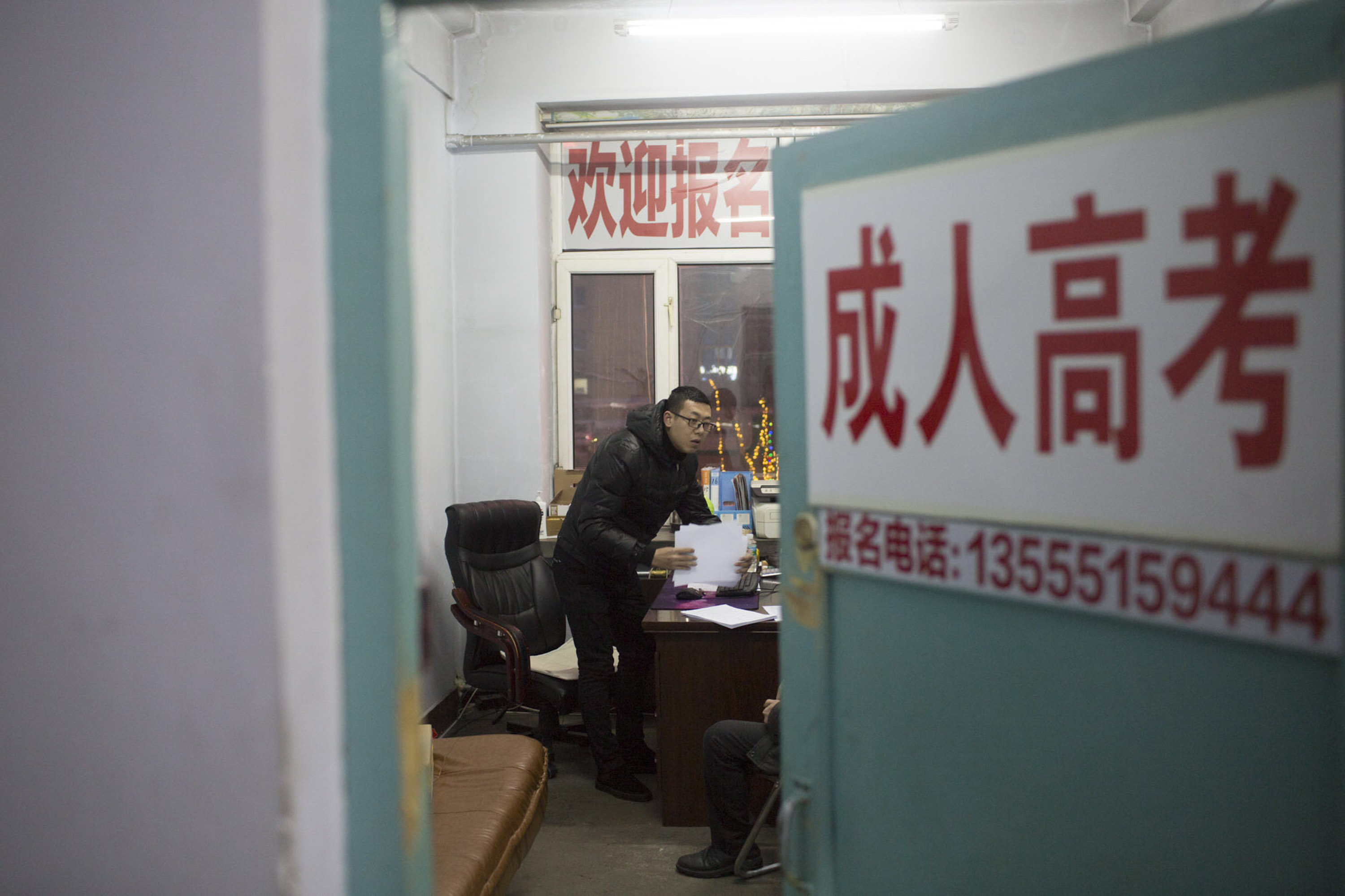 Yang Kun is visited by a client at his adult education recruitment practice in Shuangyashan, Jan. 20, 2016. Yang started the firm following a demotion at the mine where he worked previously. Zhou Pinglang/Sixth Tone