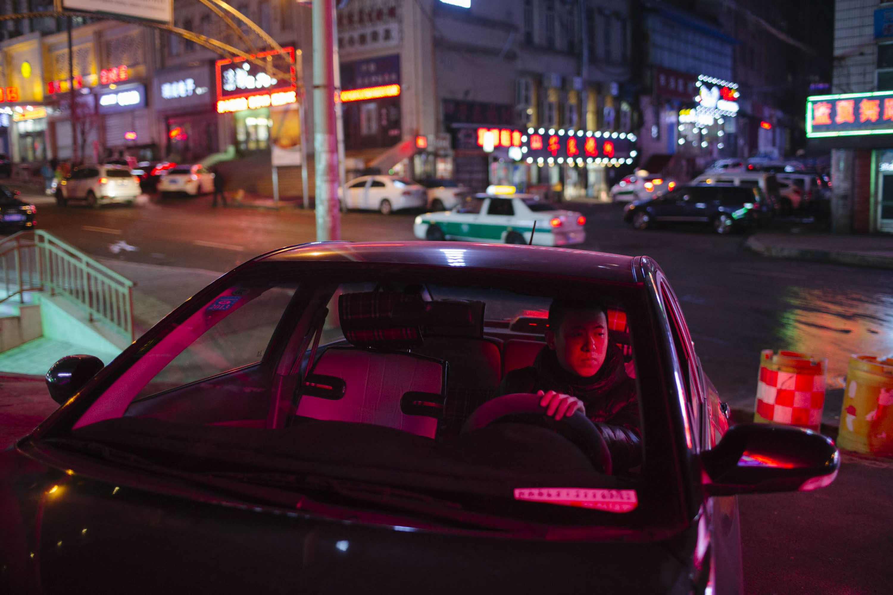 Yang Kun sits in his car at night in Shuangyashan, Jan. 17, 2016. After leaving the mining industry, the 29-year-old is managing to sustain a healthy income through a number of ventures. Zhou Pinglang/Sixth Tone