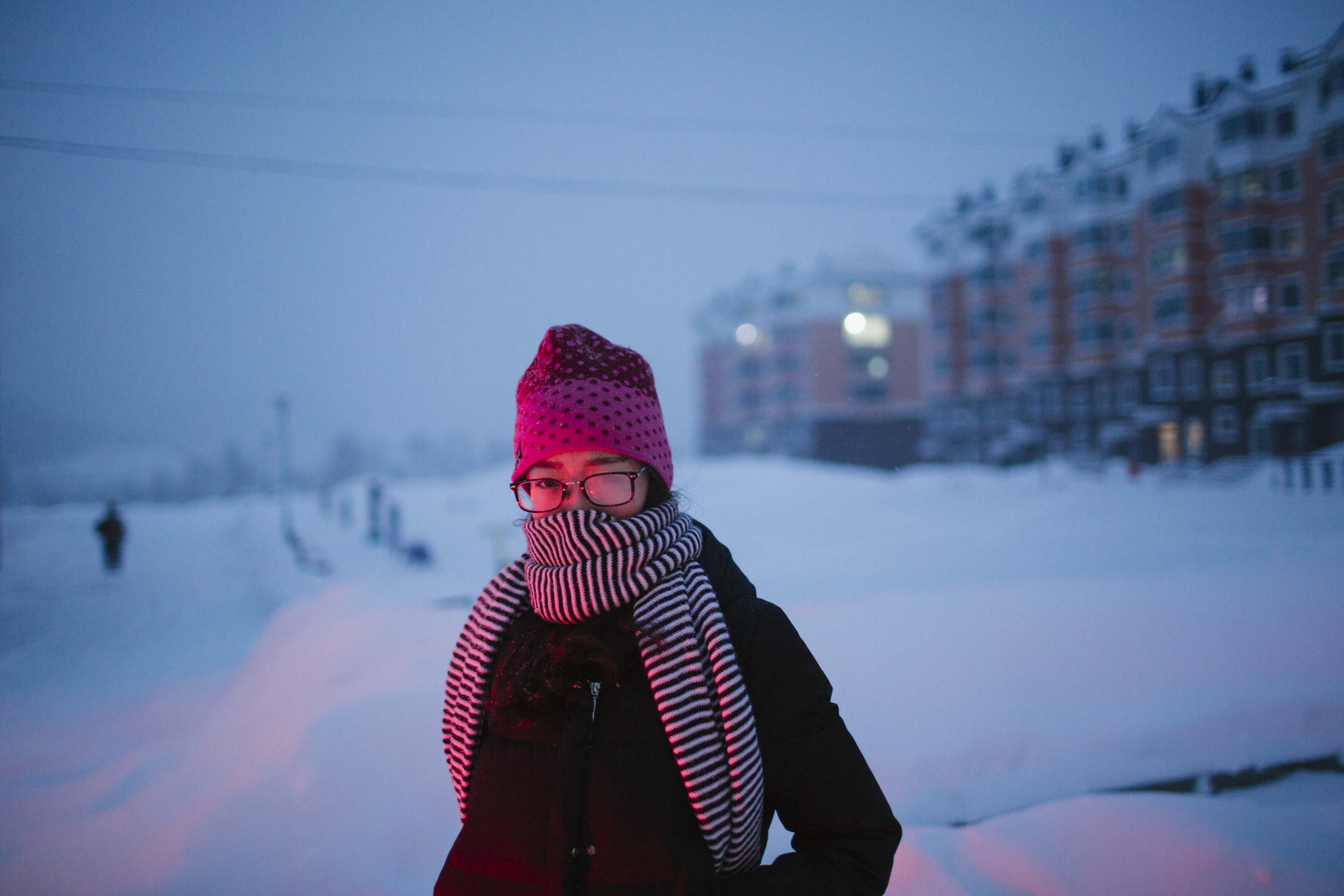 Ru Dongying walks down a snow-covered street in Shuangyashan, in front of recently built apartments, Jan. 19, 2016. Her family's home once stood here. Zhou Pinglang/Sixth Tone
