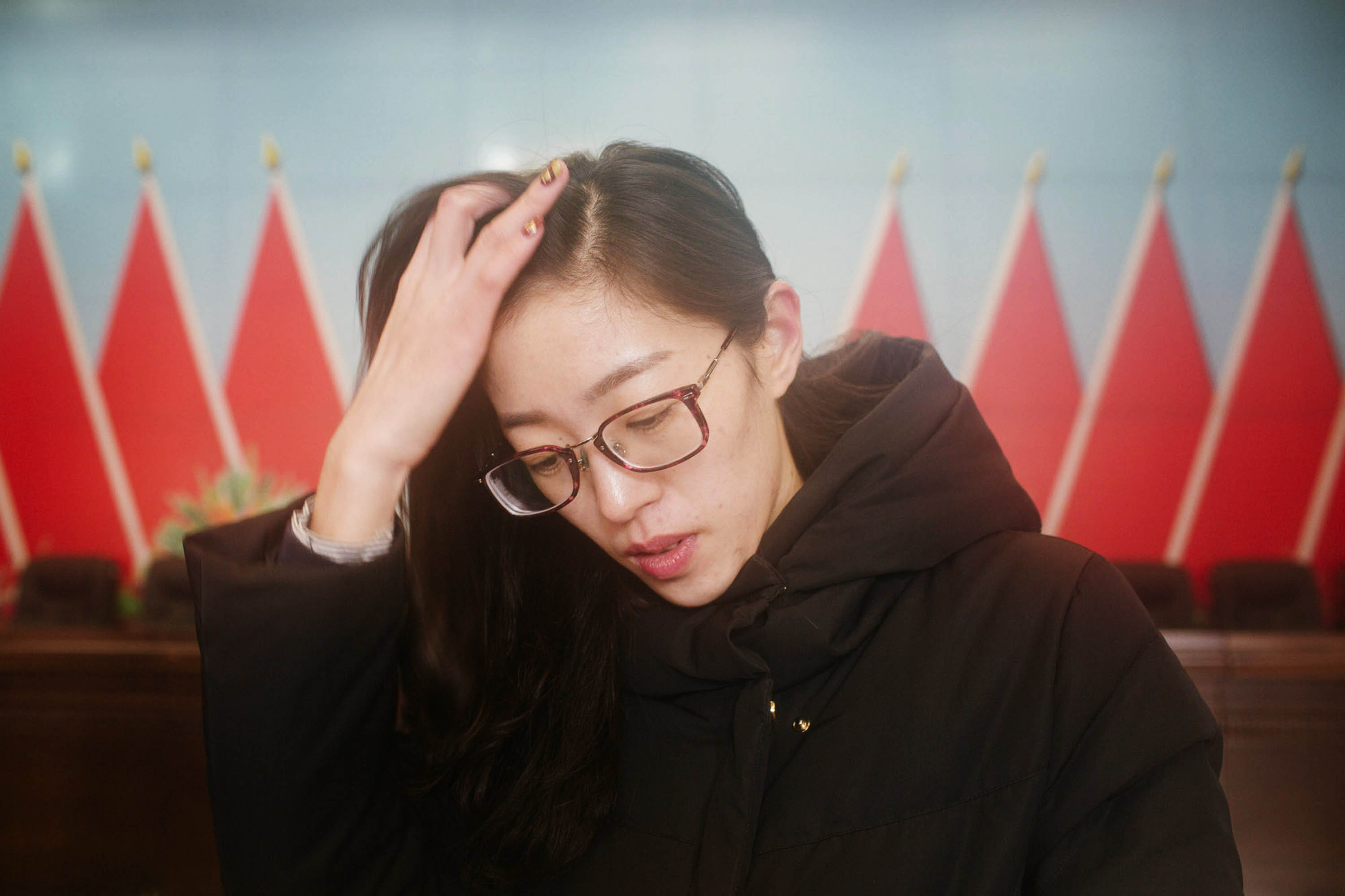 During a conference held to discuss staff restructuring, Ru Dongying waits to sign papers agreeing to the terms of her resignation, Jan. 14 2016. Ru left her job after being told she would have to face internal competition and reapply. Zhou Pinglang/Sixth Tone